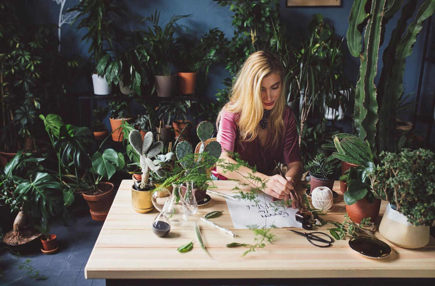 woman arranging plants thinking about choosing her perfect domain name