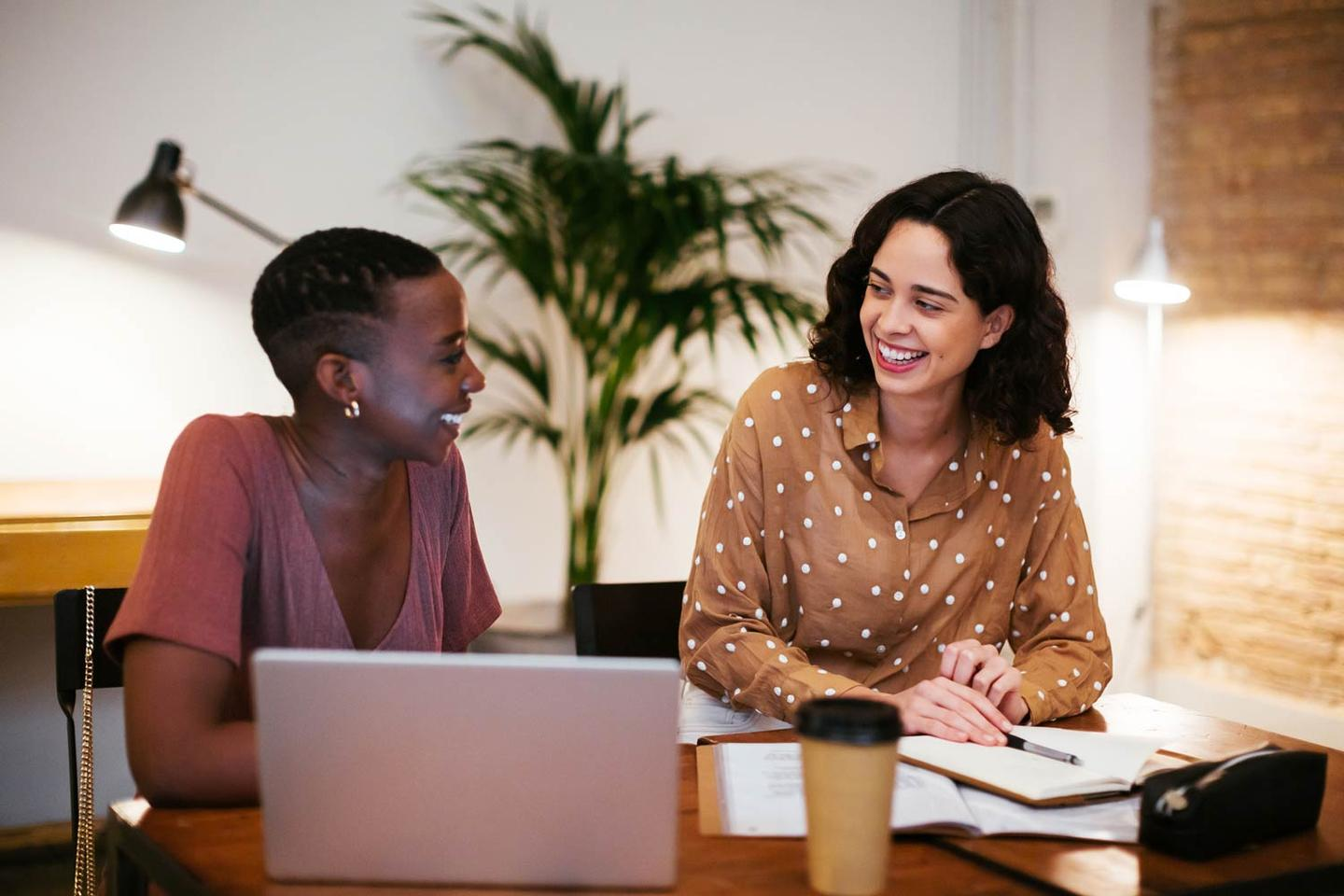 Two women smiling at each other with laptop