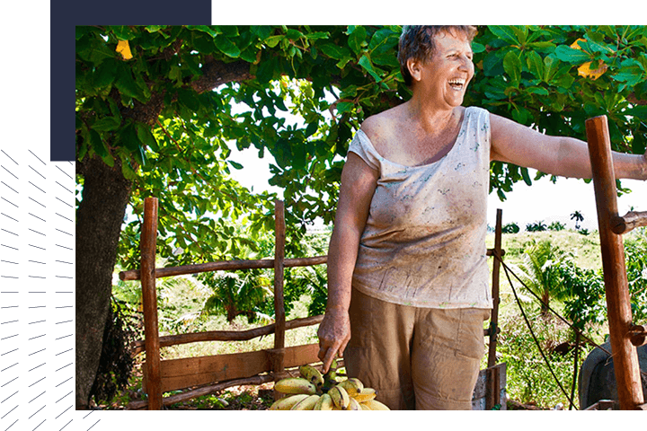 Woman volunteering and laughing while holding bananas