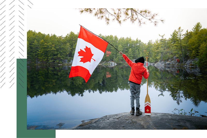 Kid holding a Canadian flag on a dock