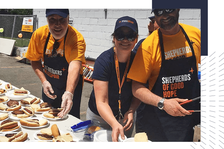 Volunteers serving hotdogs at homeless shelter