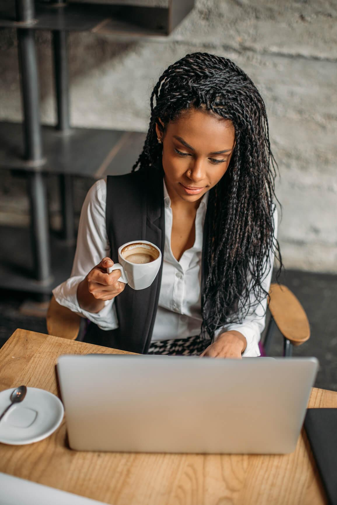 woman looking at her laptop while holding coffee