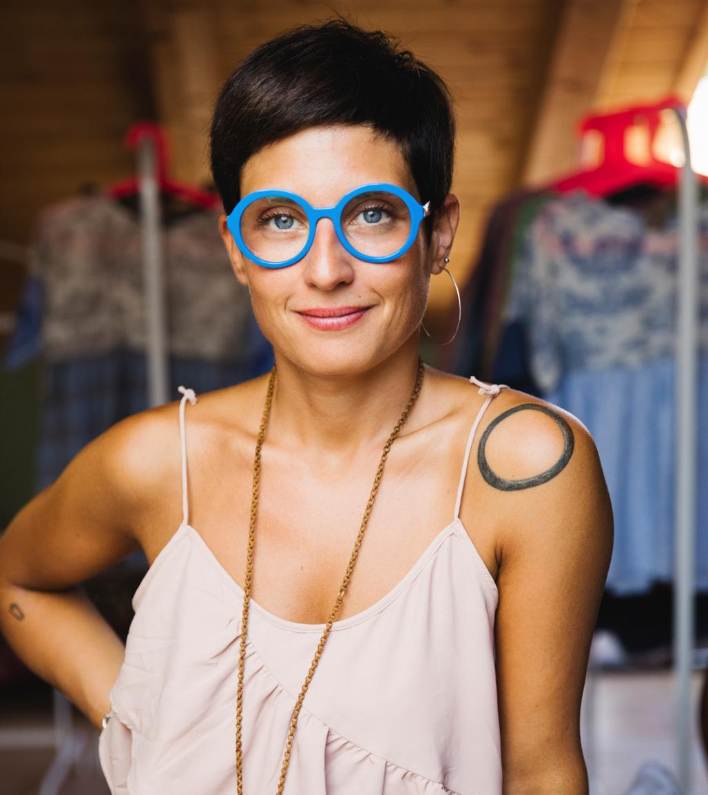 Woman with bright blue glasses and a circle tattoo